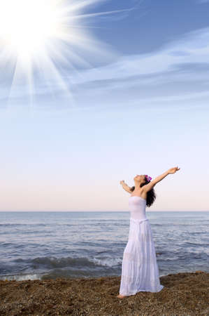 Photo for The woman in a white sundress on seacoast with open hands. Sun light - Royalty Free Image