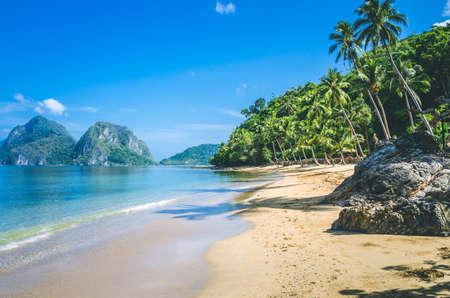 Foto de Sandy Beach with Palm Shadows, Huge Rocks in Background, El Nido, Palawan, Philippines - Imagen libre de derechos
