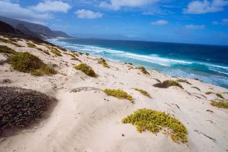 Photo for Stunning desolate landscape of sand dunes and desert plants of atlantic coastline with ocean waves. Baia Das Gatas, North of Calhau, Sao Vicente Island Cape Verde - Royalty Free Image