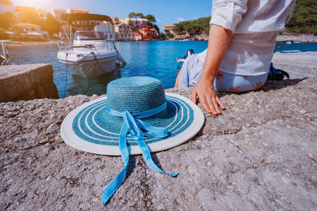 Foto de Female tourist sitting on the pier with blau sun hat at her side in Assos village in front of emerald bay of Mediterranean sea and beautiful traditional houses of in Kefalonia, Greece - Imagen libre de derechos