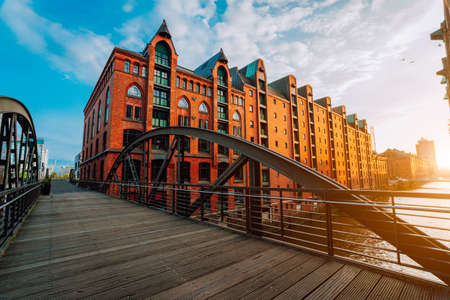 Photo for Pedestrian arch bridge over canals in the Speicherstadt of Hamburg. Warm golden hour sunset light on red bricks buildings - Royalty Free Image