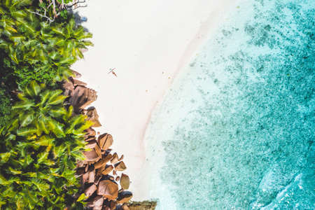 Photo for Aerial photo of exotic tropical white sand beach with young woman sunbathing relaxing. Concept of travel vacation holidays in paradise - Royalty Free Image