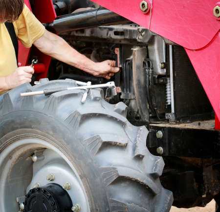 Photo pour Man repairs large red tractor with focus on tools and front wheel - image libre de droit