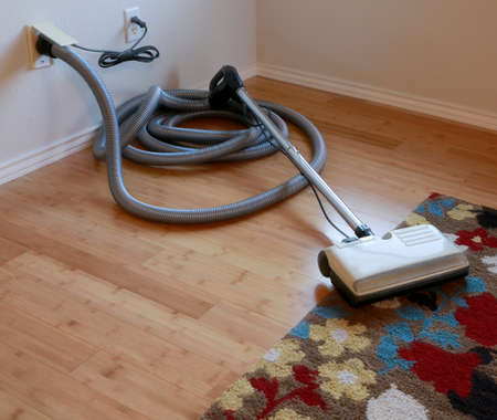 Photo pour Cleaning contest: Beautiful bamboo hardwood floor and wool rug with a central vacuum cleaner attached to the wall - image libre de droit