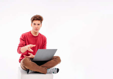 Photo pour Teenager student working at laptop on white background - image libre de droit