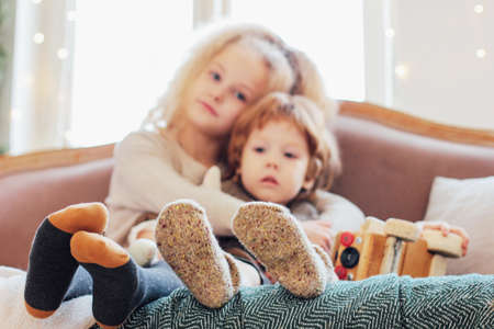 Photo pour Sister hugs little brother on the couch, focus on legs in warm socks, cozy mood - image libre de droit