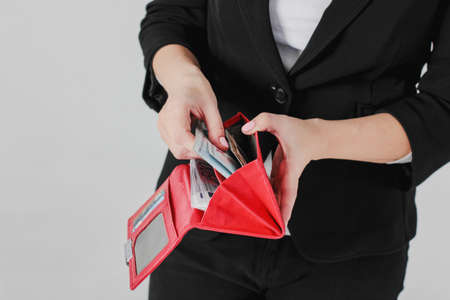 Foto de Women hands take money from red purse on gray background isolated close up - Imagen libre de derechos