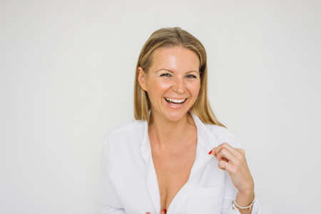 Foto de Portrait of happy blonde forty year woman with long hair in the white shirt on wall background isolated - Imagen libre de derechos