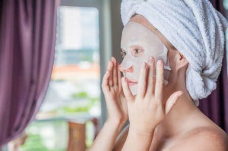 Photo pour Young red-haired woman doing facial mask sheet. Beauty and Skin Care Concept - image libre de droit