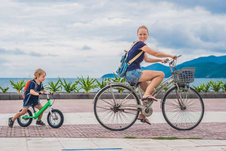 Foto de Happy family is riding bikes outdoors and smiling. Mom on a bike and son on a balancebike. - Imagen libre de derechos