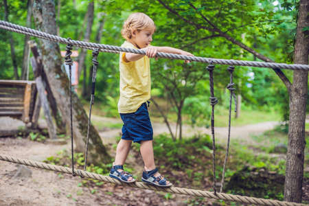 Photo pour Portrait of cute little boy walks on a rope bridge in an adventure rope park. - image libre de droit