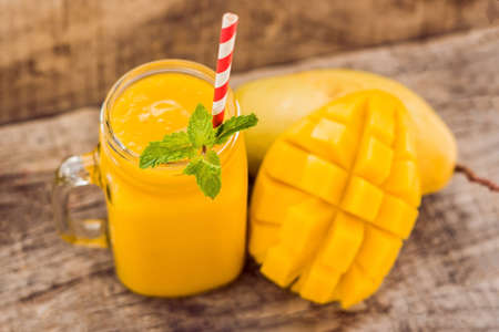 Foto de Healthy ripe Yellow Mango Smoothie, Mango fruit and mango cubes on the wooden table, concept healthy food. - Imagen libre de derechos