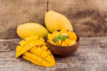 Foto de Mango fruit and mango cubes on the wooden table. - Imagen libre de derechos