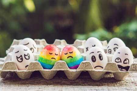 Photo pour discrimination gay concept. Two rainbow eggs in the form of a homosexual couple. And condemning people around. - image libre de droit