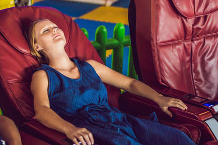 Foto de Beautiful young lady relaxing in the massage chair. - Imagen libre de derechos