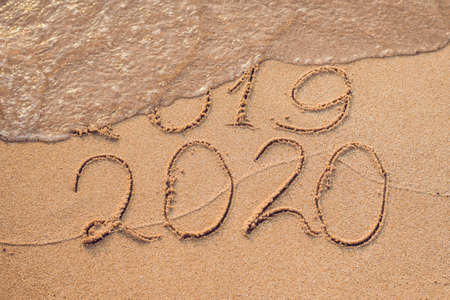 Foto de New Year 2020 is coming concept - inscription 2019 and 2020 a beach sand, the wave is almost covering the digits 2019. - Imagen libre de derechos