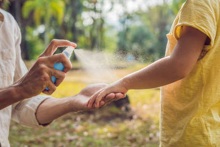 Photo pour dad and son use mosquito spray.Spraying insect repellent on skin outdoor. - image libre de droit
