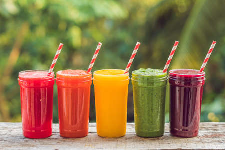 Photo for Rainbow from smoothies. Watermelon, papaya, mango, spinach and dragon fruit. Smoothies, juices, beverages, drinks variety with fresh fruits on a wooden table. - Royalty Free Image