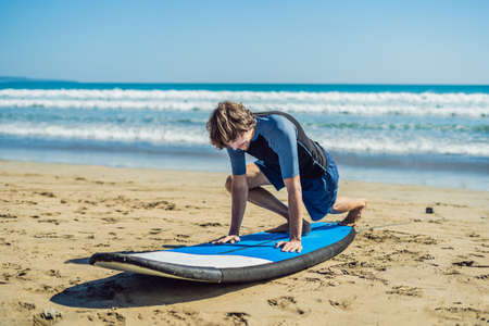 Photo pour Young man surfer training before go to lineup on a sand beach. Learning to surf. Vacation concept. Summer holidays. Tourism, sport. - image libre de droit
