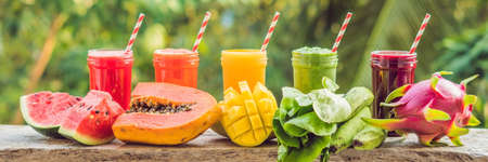 Photo for Rainbow from smoothies. Watermelon, papaya, mango, spinach and dragon fruit. Smoothies, juices, beverages, drinks variety with fresh fruits on a wooden table. BANNER, long format - Royalty Free Image
