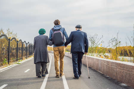 Foto de An elderly couple walks in the park with a male assistant or adult grandson. - Imagen libre de derechos