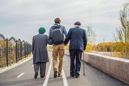 Foto de An elderly couple walks in the park with a male assistant or adult grandson. Caring for the elderly, volunteering. - Imagen libre de derechos