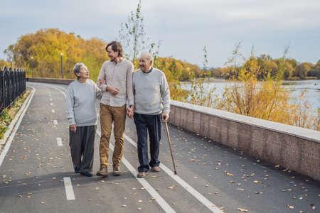 Foto de An elderly couple walks in the park with a male assistant or adult grandson. - Imagen libre de derechos