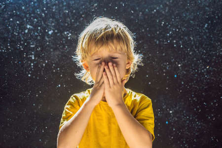 Photo pour Allergy to dust.Boy sneezes because he is allergic to dust. Dust flies in the air backlit by light. - image libre de droit