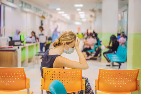 Foto de Young woman sitting in hospital waiting for a doctors appointment. Patients In Doctors Waiting Room - Imagen libre de derechos