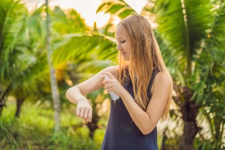 Foto de Woman spraying insect repellent on skin outdoor - Imagen libre de derechos