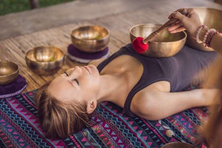 Foto de Nepal Buddha copper singing bowl at spa salon. Young beautiful woman doing massage therapy singing bowls in the Spa against a waterfall. Sound therapy, recreation, meditation, healthy lifestyle and body care concept - Imagen libre de derechos