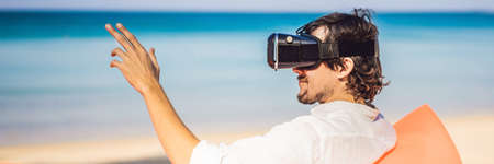 Foto de BANNER, LONG FORMAT Summer lifestyle portrait of man sitting on the orange inflatable sofa and uses virtual reality headset on the beach of tropical island. Relaxing and enjoying life on air bed - Imagen libre de derechos
