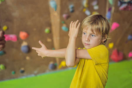 Photo pour The boy is warming up before climbing a rock wall indoor - image libre de droit