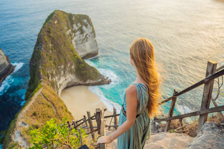 Foto de Family vacation lifestyle. Happy woman stand at viewpoint. Look at beautiful beach under high cliff. Travel destination in Bali. Popular place to visit on Nusa Penida island. - Imagen libre de derechos