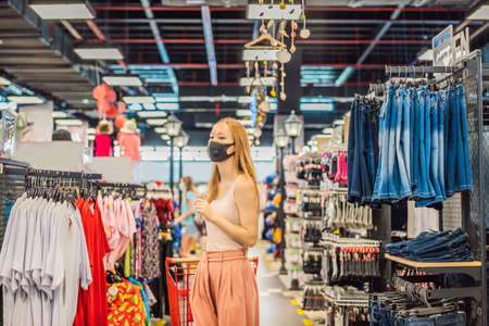 Photo pour Woman in a clothing store in a medical mask because of a coronovirus. Quarantine is over, now you can go to the clothing store - image libre de droit
