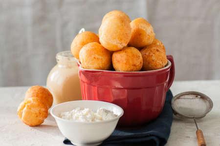 Foto de Small cottage cheese doughnuts (castgnole) served on a red  bowl. - Imagen libre de derechos