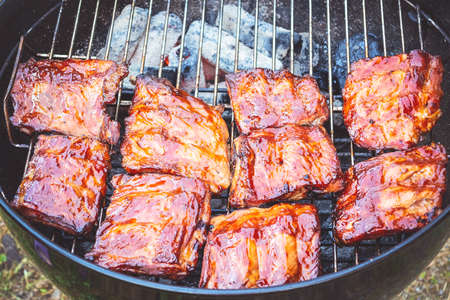 Photo for Grilled pork ribs on round bbq grill - Royalty Free Image