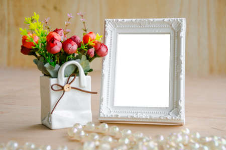 Photo pour Flowers vase and blank white picture frame on wooden background - image libre de droit