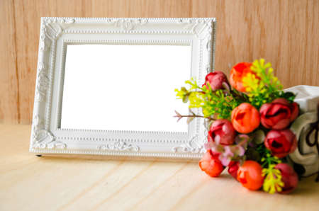 Photo for Flowers vase and vintage white picture frame on wooden desktop, clipping path - Royalty Free Image
