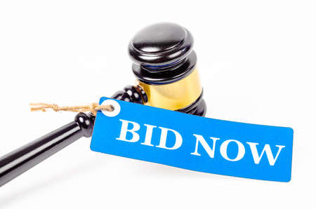 Foto de Bid now text on paper tag with wooden gavel auction isolated on white background. - Imagen libre de derechos