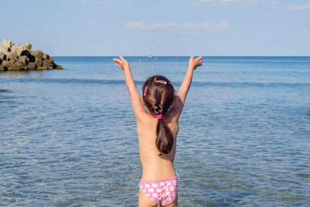 Photo for Girl plays at the sea - Royalty Free Image