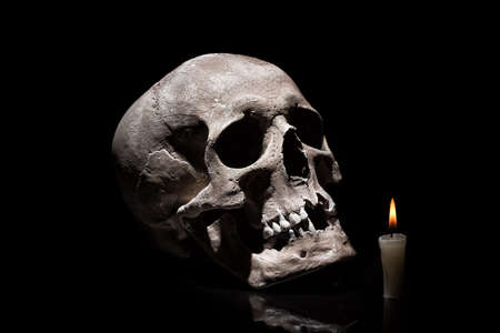 Photo pour Human skull with burning candle on black background with reflection close up. - image libre de droit