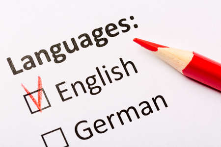 Photo for Questionnaire concept. Languages with English and German checkboxes with red pencil. Close up image. - Royalty Free Image