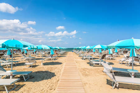 Foto de Beach chairs and umbrellas in Rimini, Italy during summer day with blue sky. Summer vacation and relax concept - Imagen libre de derechos