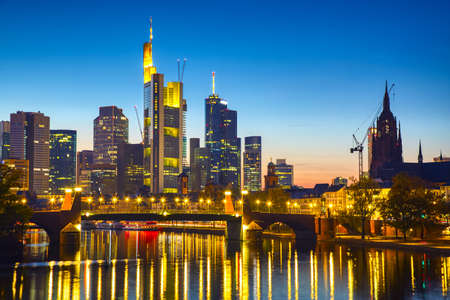 Foto de Panoramic view cityscape skyline of business district with skyscrapers and mirror reflections in the river Main during sunset blue hour, Frankfurt am Main. Hessen, Germany. - Imagen libre de derechos