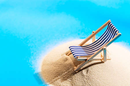 Foto de Miniature beach with beach chair lounger. Island in an ocean. Sand and ocean. Tropical resort and vacation concept - Imagen libre de derechos