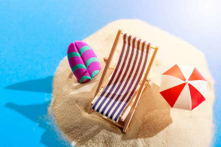 Foto de Miniature beach with deck chair, umbrella, parasol and surfboard on tropical islands sand surrounded by water. Tropical resort and vacation concept - Imagen libre de derechos