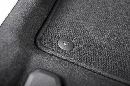 Photo for Corner of car mat with floor holder in white car interior - Royalty Free Image