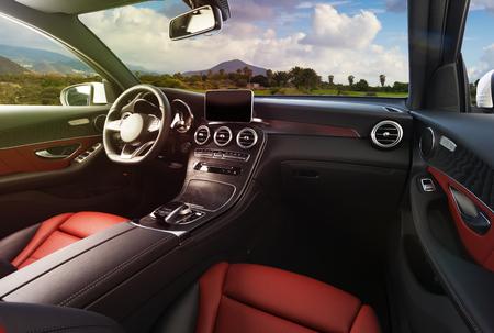 Foto de Modern luxury car Interior - steering wheel, shift lever and dashboard. Car interior luxury inside. Steering wheel, dashboard, speedometer, display. Red and black leather cockpit - Imagen libre de derechos