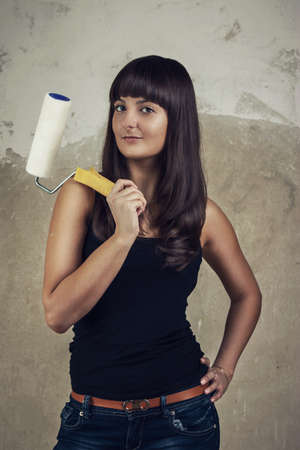 beautiful young girl holding paint roller over grunge background